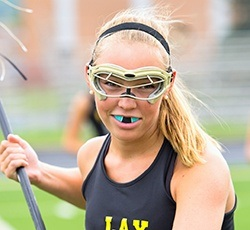 Teen girl playing lacrosse with blue mouthguard