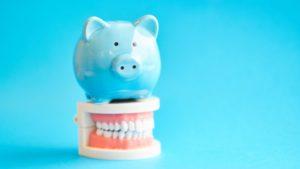 light blue piggy bank on top of set of false teeth