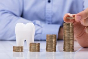 Model tooth and coin piles demonstrating are dental implants in Greybull worth the cost