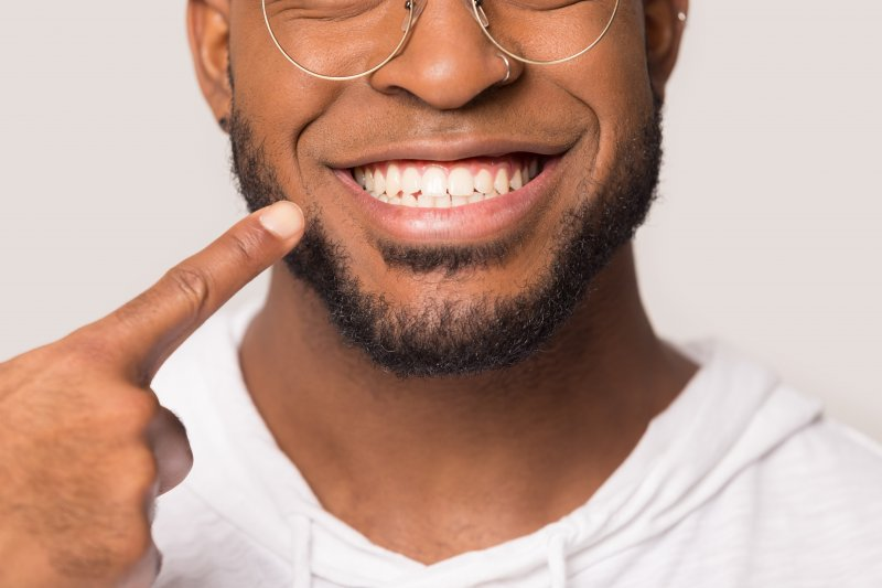 Smiling man in white shirt pointing to his teeth